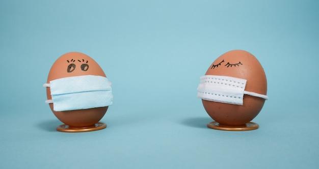 Ovos de páscoa em uma máscara para decorar as férias da páscoa em um fundo azul com copyspace