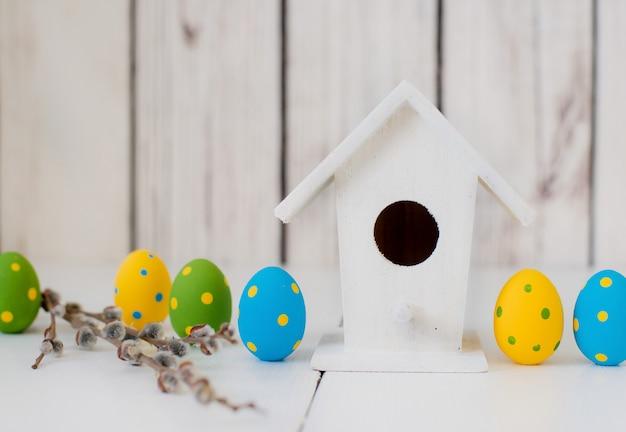 Ovos de páscoa em uma parede de madeira branca