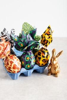 Ovos de páscoa embrulhados em papel de impressão animal