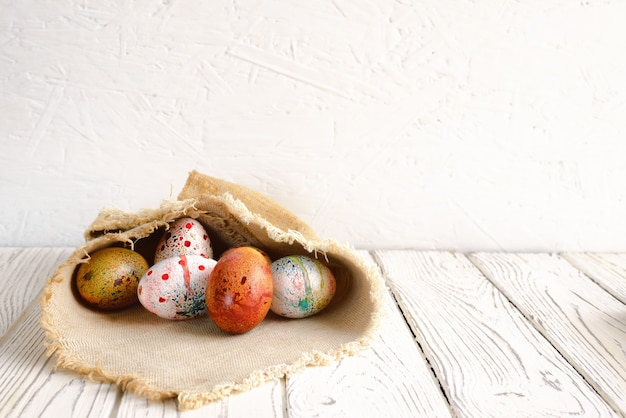 Ovos de páscoa embrulhados em tecido de lona no fundo claro
