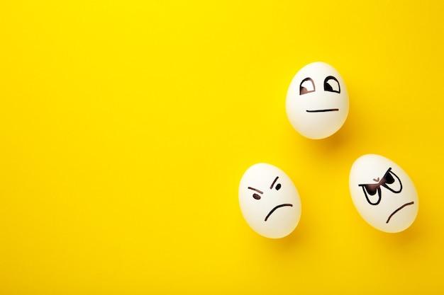 Ovos de páscoa engraçados com diferentes emoções no rosto em fundo amarelo.