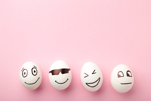 Ovos de páscoa engraçados com diferentes emoções no rosto em fundo rosa.