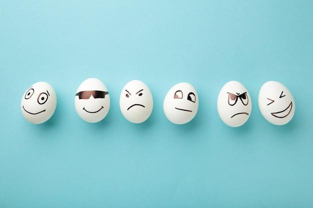 Ovos de páscoa engraçados com diferentes emoções no rosto sobre fundo azul.