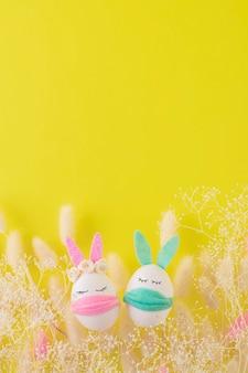 Ovos de páscoa engraçados em máscaras médicas em um fundo amarelo brilhante.
