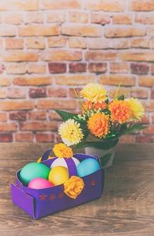 Ovos de páscoa festivos coloridos na cesta de papel. tonificado sob o filme antigo, adicionado granulação e ruído