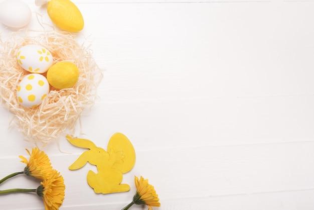 Ovos de páscoa, flores, coelho amarelo. mesa festiva de primavera. camada plana, vista superior, espaço de cópia