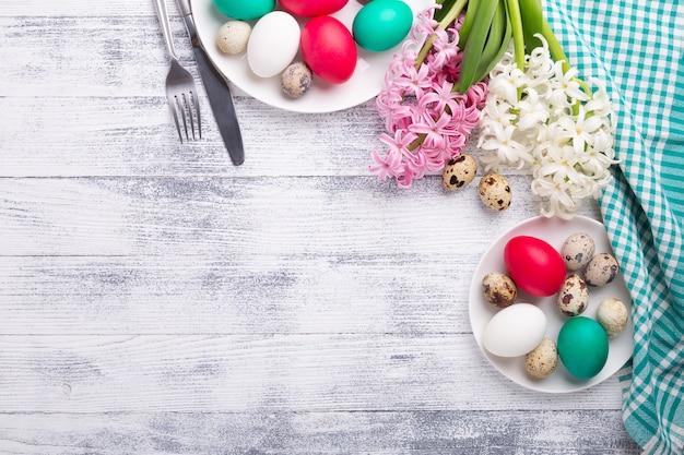 Ovos de páscoa, jacinto rosa e branco sobre fundo de madeira. conceito de páscoa vista do topo. copie o espaço