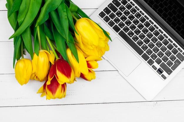 Ovos de páscoa, laptop e buquê de tulipas.