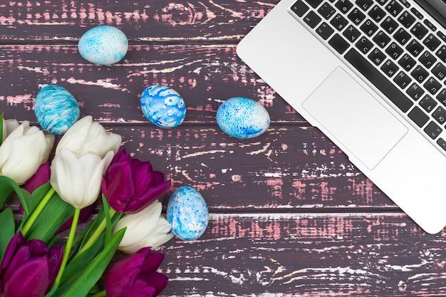 Ovos de páscoa, laptop e buquê de tulipas