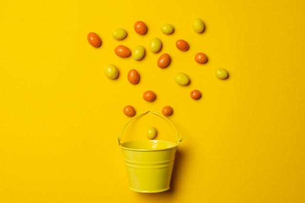 Ovos de páscoa laranja e amarelo sobre um fundo amarelo sobre um balde