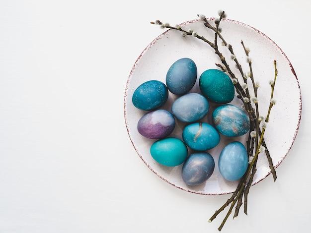 Ovos de páscoa multi-coloridas, galhos salgueiros e placa velha