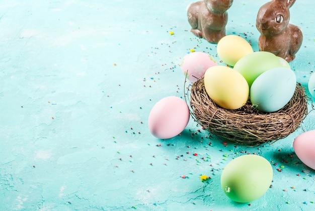 Ovos de páscoa multicoloridos com ninho de pássaro decorativo e açúcar polvilha sobre um azul claro,