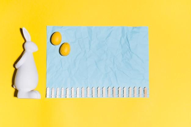 Ovos de páscoa na folha de papel com coelho na mesa