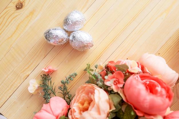 Ovos de páscoa na mesa de madeira branca. flores e doces ao redor.