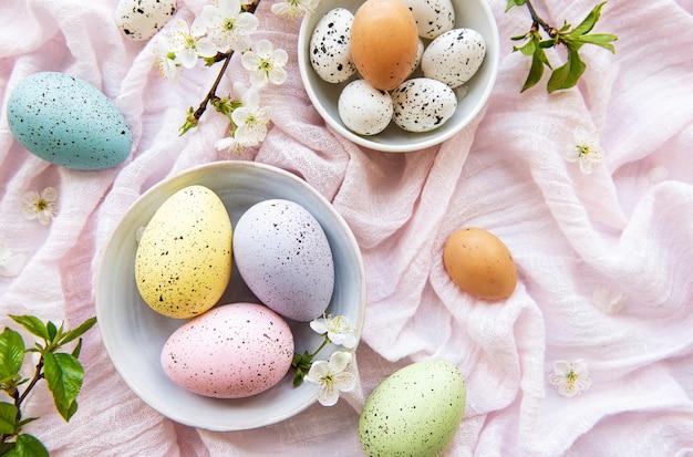 Ovos de páscoa na mesa de tecido rosa com flor de cerejeira na primavera