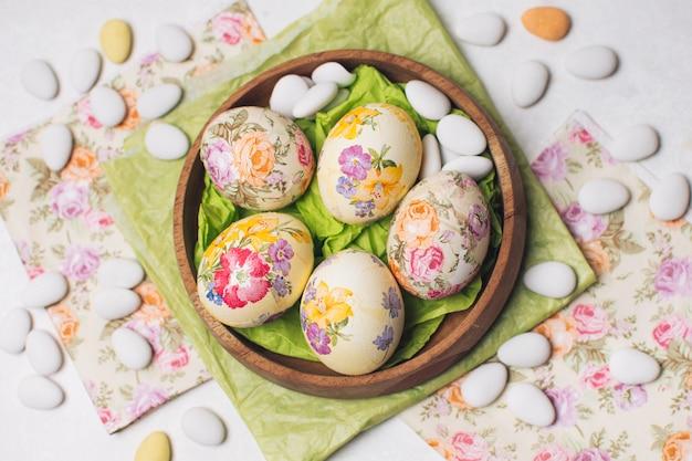 Ovos de páscoa na tigela entre guardanapos e pedrinhas