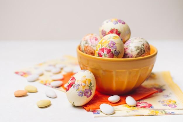 Ovos de páscoa na tigela perto de guardanapos e pedrinhas