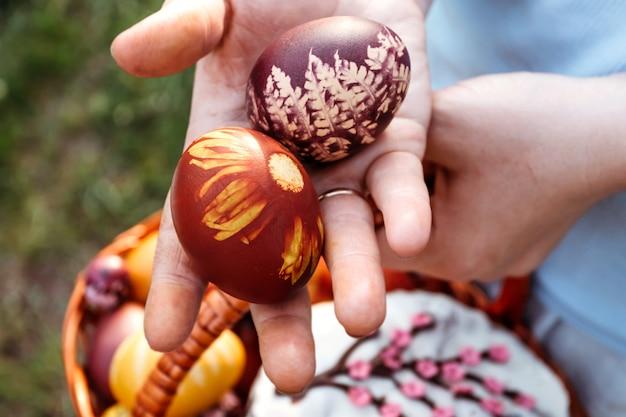 Ovos de páscoa nas mãos femininas sobre fundo azul brilhante.