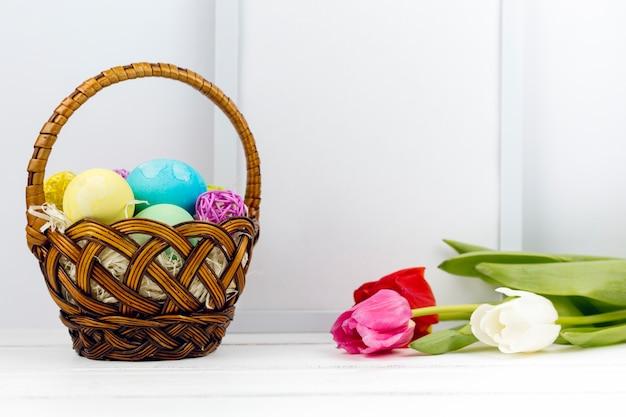 Ovos de páscoa no cesto com tulipas e moldura em branco na mesa