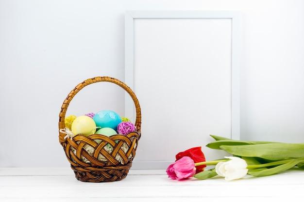 Ovos de páscoa no cesto com tulipas e moldura em branco