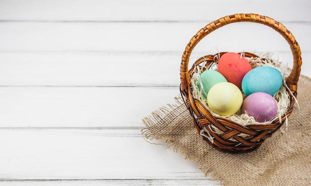 Ovos de páscoa no cesto na mesa de madeira