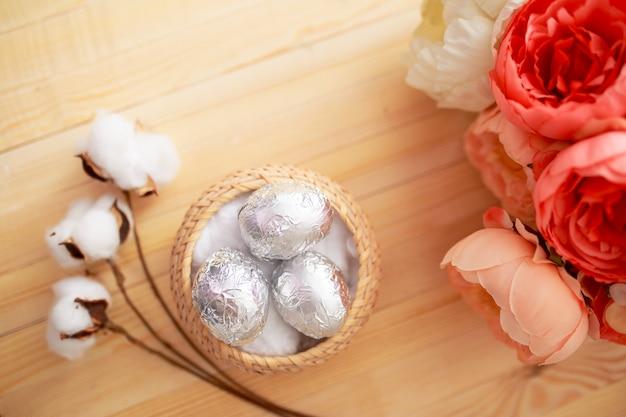 Ovos de páscoa no fundo de madeira branco com flores ao redor. ovos cobertos com papel alumínio.