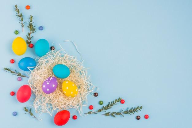 Ovos de páscoa no ninho com galhos de plantas na mesa azul