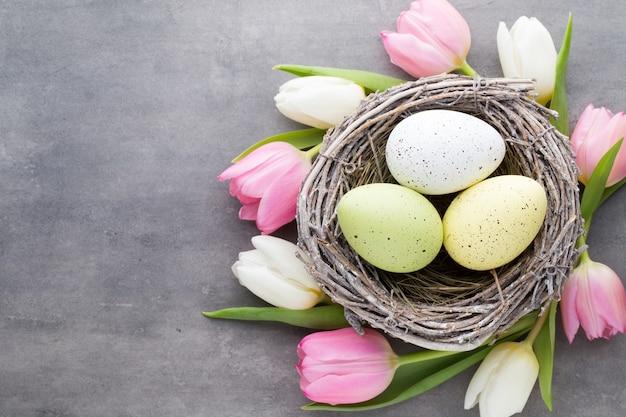 Ovos de páscoa no ninho com tulipas ao redor