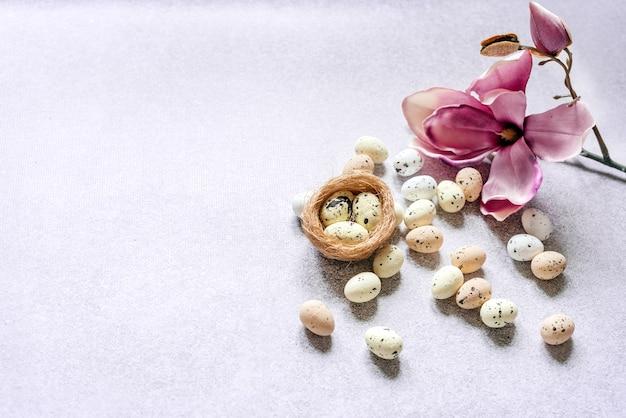 Ovos de páscoa no ninho do pássaro e flor de magnólia roxa com espaço de cópia.