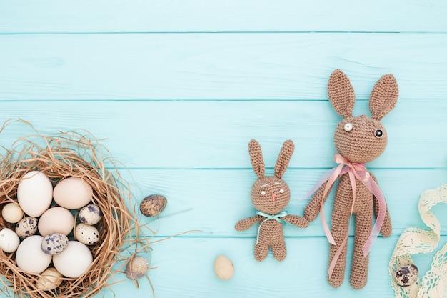 Ovos de páscoa no ninho e coelhos de malha feitos à mão sobre fundo azul. postura plana.
