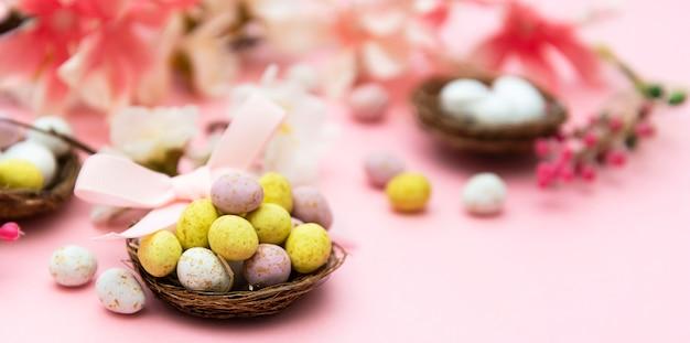 Ovos de páscoa no ninho em fundo rosa. banner de primavera