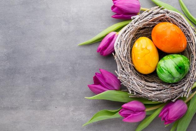 Ovos de páscoa no ninho, flores da primavera, tulipas