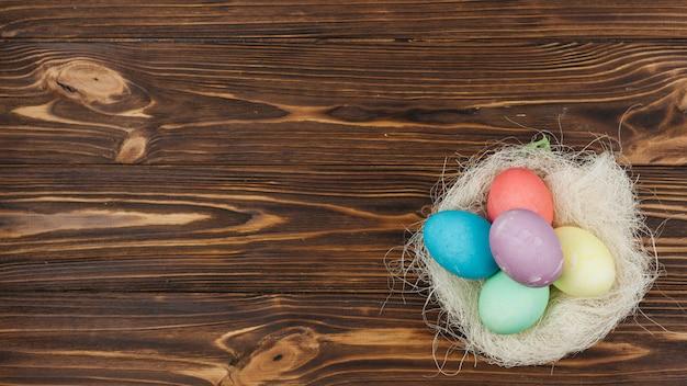 Ovos de páscoa no ninho na mesa de madeira
