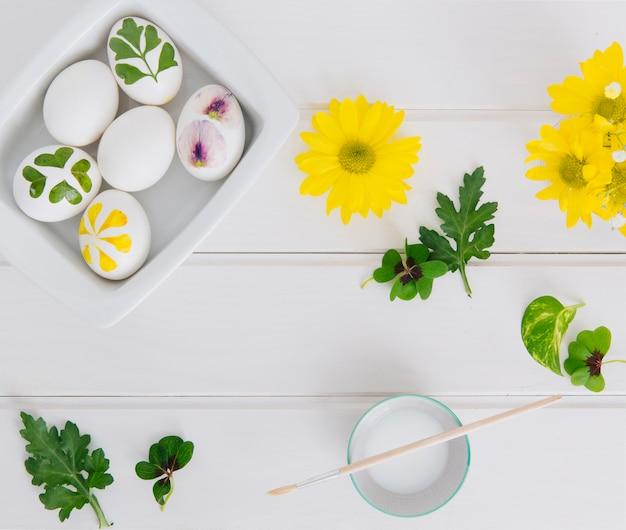 Ovos de páscoa no recipiente perto de flores, folhas e copo com líquido de tintura