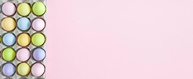 Ovos de páscoa pastel coloridos em rosa, vista superior com luz natural. estilo liso leigo.