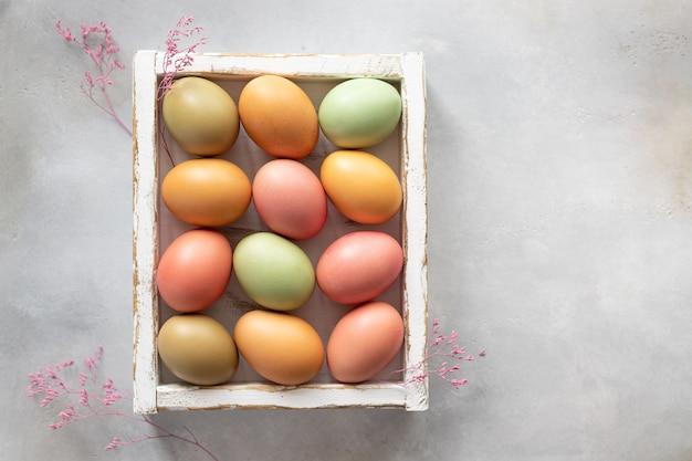 Ovos de páscoa pastel em caixa de madeira branca. tintura de ovo natural