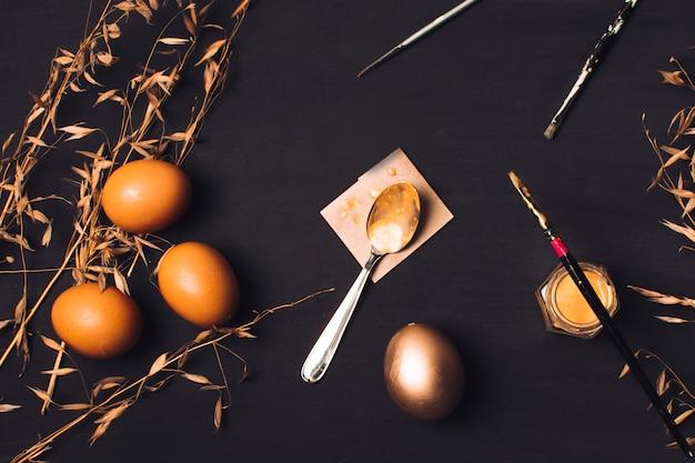 Ovos de páscoa perto de colher no papel e pincel na lata de corante entre plantas