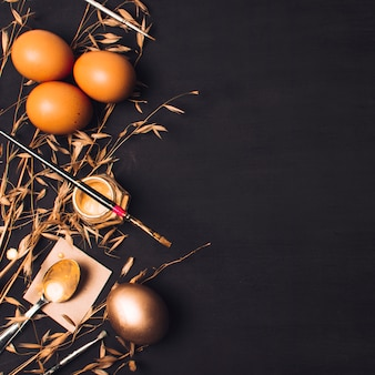 Ovos de páscoa perto de colher no papel e pincel na tintura pode entre plantas secas