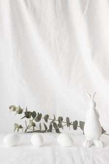 Ovos de páscoa perto de galhos de plantas e figura de coelho