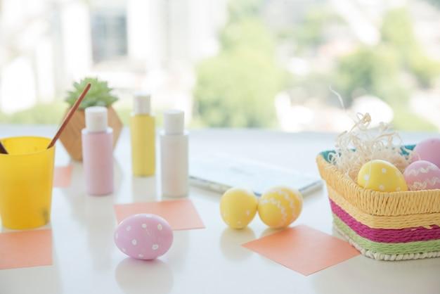 Ovos de páscoa perto de papéis e cores na mesa