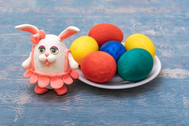 Ovos de páscoa pintados à mão e um coelho de plasticina artesanal em uma saia rosa sobre um fundo azul de madeira