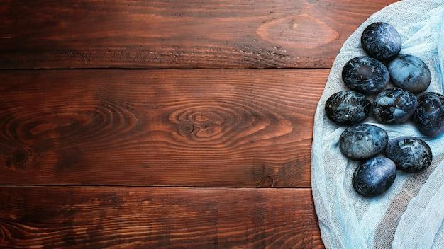 Ovos de páscoa pintados de azuis em tecido e fundo de madeira
