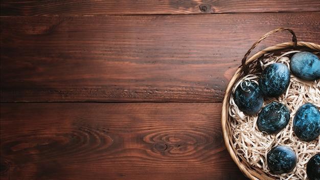 Ovos de páscoa pintados de azuis em uma cesta em um fundo de madeira