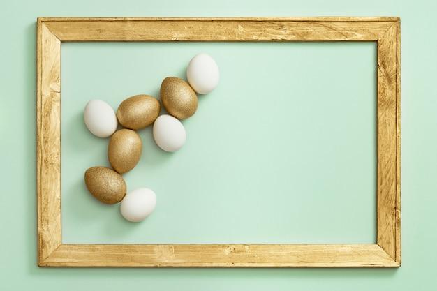 Ovos de páscoa pintados de branco e dourado em papel verde claro com moldura de madeira. conceito mínimo de páscoa.