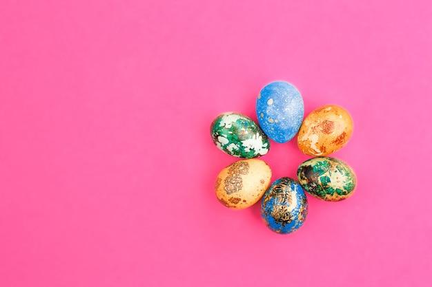 Ovos de páscoa pintados em azul, verde e amarelo mentem em um círculo. ovos de páscoa pintados em um fundo rosa. postura plana. copie o espaço.