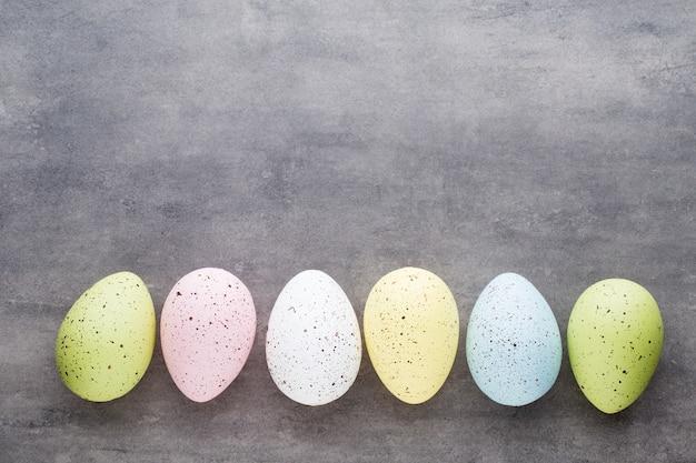Ovos de páscoa pintados em cores sobre um fundo padrão.