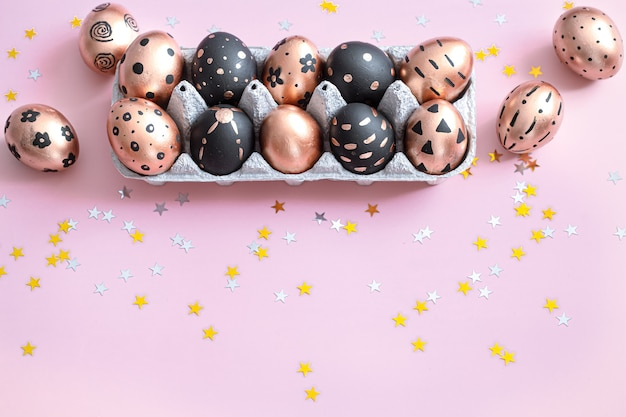 Ovos de páscoa pintados festivos na parede rosa.