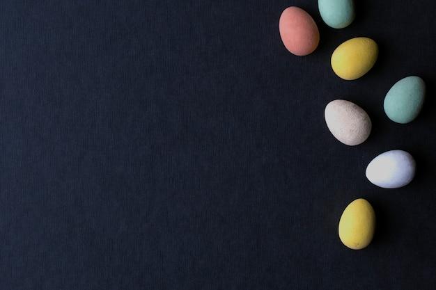 Ovos de páscoa pintados várias cores sobre fundo preto, design moderno de vista superior