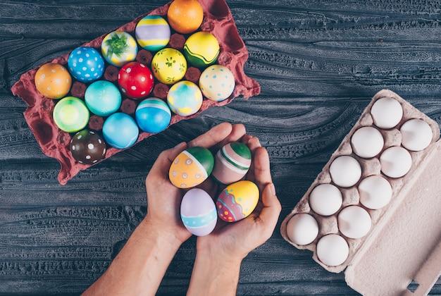 Ovos de páscoa plana leigos em desenhos animados de ovo com man_s mãos cheias de ovos no fundo escuro de madeira.