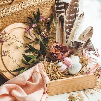 Ovos de páscoa rosa em um ninho com decorações florais e penas perto da janela